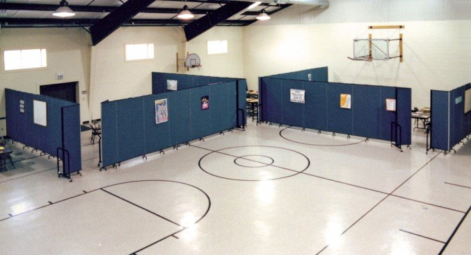 Screenflex Room Dividers are arranged in a gymnasium to create classrooms along the walls