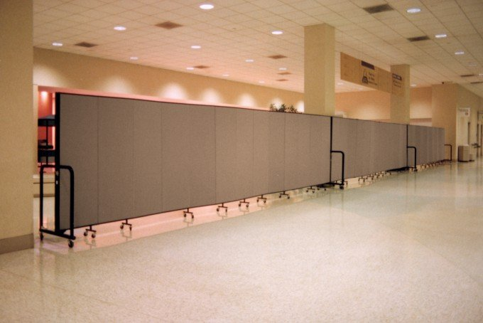 3 Room Divider units are connected to form a long wall separating a construction area from guest services