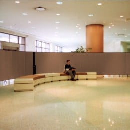 Two room dividers connected to form a long continuous curved wall in a lobby