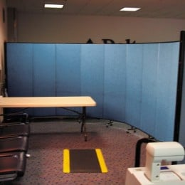 A curved wall created with a Screenflex Room Divider provides a barrier for airport security indpecting luggage and parcels