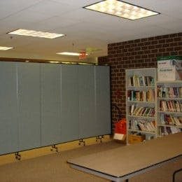 Book shelves line a brick wall next to a portable room divider wall