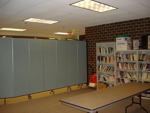 Book shelves line a brick wall next to a portable room divider wall
