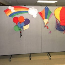 Colorful fabric kites tacked to a Screenflex Room Divider
