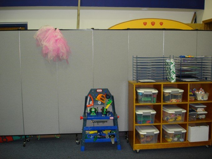 Screenflex Portable Partition Divides a classroom into a play and learning area