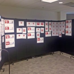 Different corporate advertising ideas are displayed on a black room divider