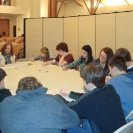 A group of teens sit around a table in a room created with room dividers inside a sanctuary
