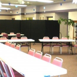 A large fellowship hall is divided into two party rooms with a Screenflex Room Divider