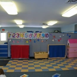 A room divider splits a day care center room into play and leaning areas
