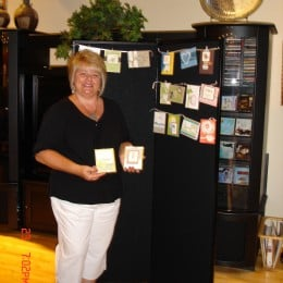 A female hangs homemade Stampin Up cards on a black Screenflex Display unit