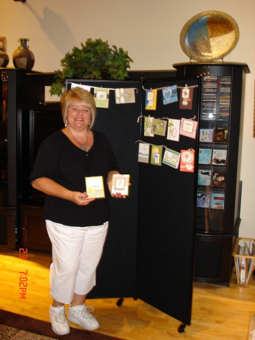 A woman stands next to a black display tower showcasing handmade cards
