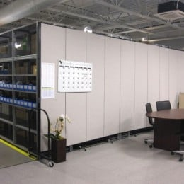 A room divider forms a wall between warehouse storage shelves and an employee's desk