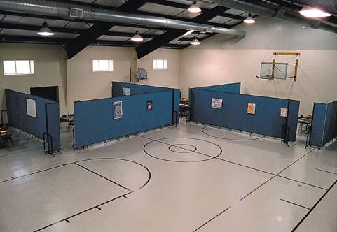 Blue portable walls arranged in a gym to create Sunday school rooms