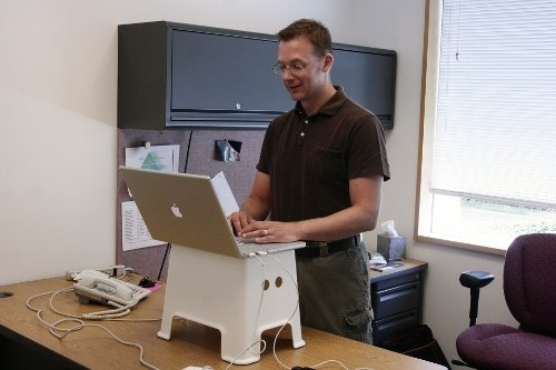 A man is standing working on his laptop computer that is resting on footstool on top of his desk