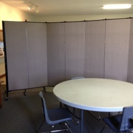 A room divider separates a round table and 4 chairs from a fellowship hall