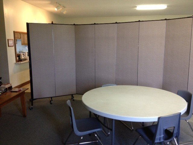 A Screenflex Room Divider divides a round table and chairs from a church dining room