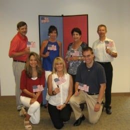 A group of men and women holding small American Flags pose in front of a red and blue diplay board