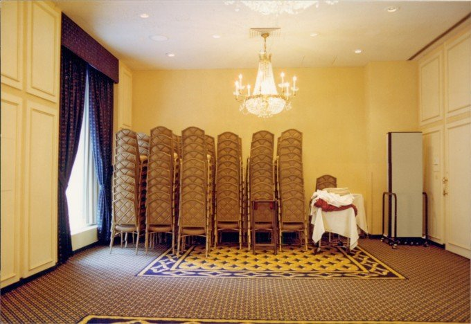 12 tall stacks of banquet chairs in the rear of a banquet room