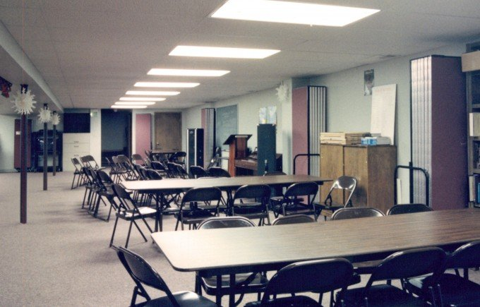 Rows of tables and chairs in a church basement