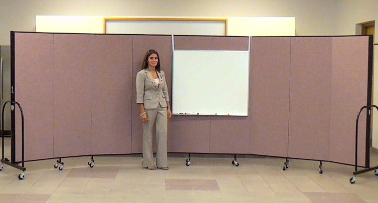 A teacher stands beside a portable dry erase board hung on a Screenflex Room Divider