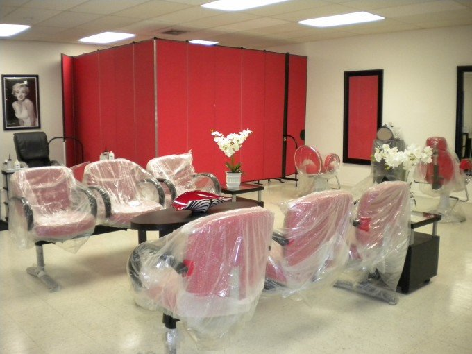 A red portable room divider with a door sections off the rear corner of a salon to create an employee workstation