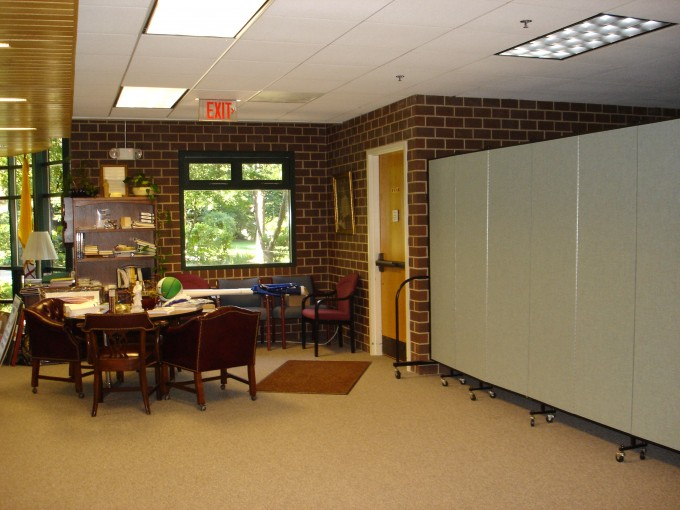 A large room is divided in two with a room divider