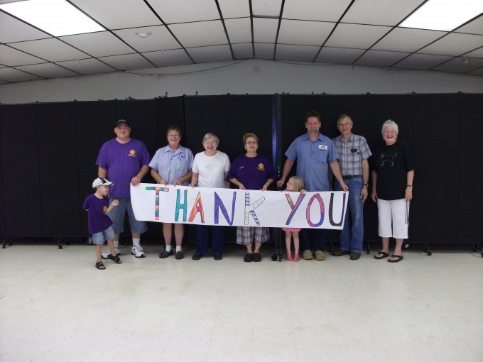 Happy customers hold a thank you sign up for their Screenflex room dividers