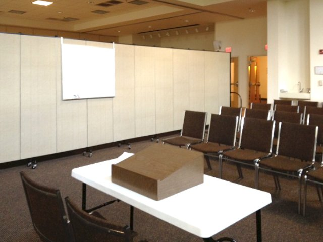 Dry erase board hanging from a room divider in a conference room