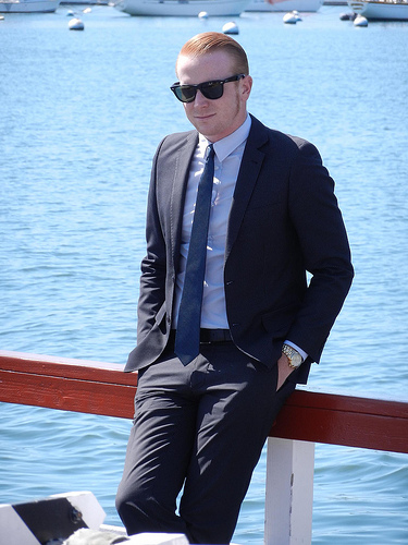 A man sits on a boat railing in a dark suit and sunglasses