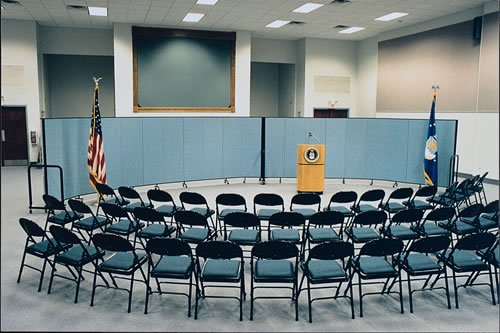 Two Screenflex Room Dividers form a curved wall in a makeshift US governement press room.