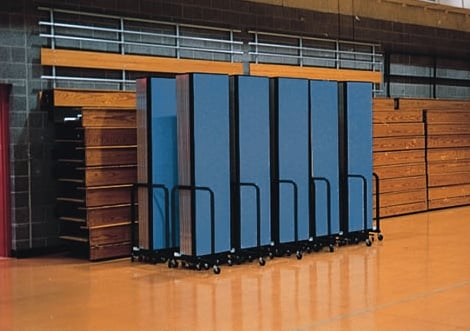 Blue Screenflex Room Dividers fodled and stored against wooden bleachers
