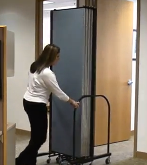 A model rolls a Screenflex Room Divider through a standard doorway