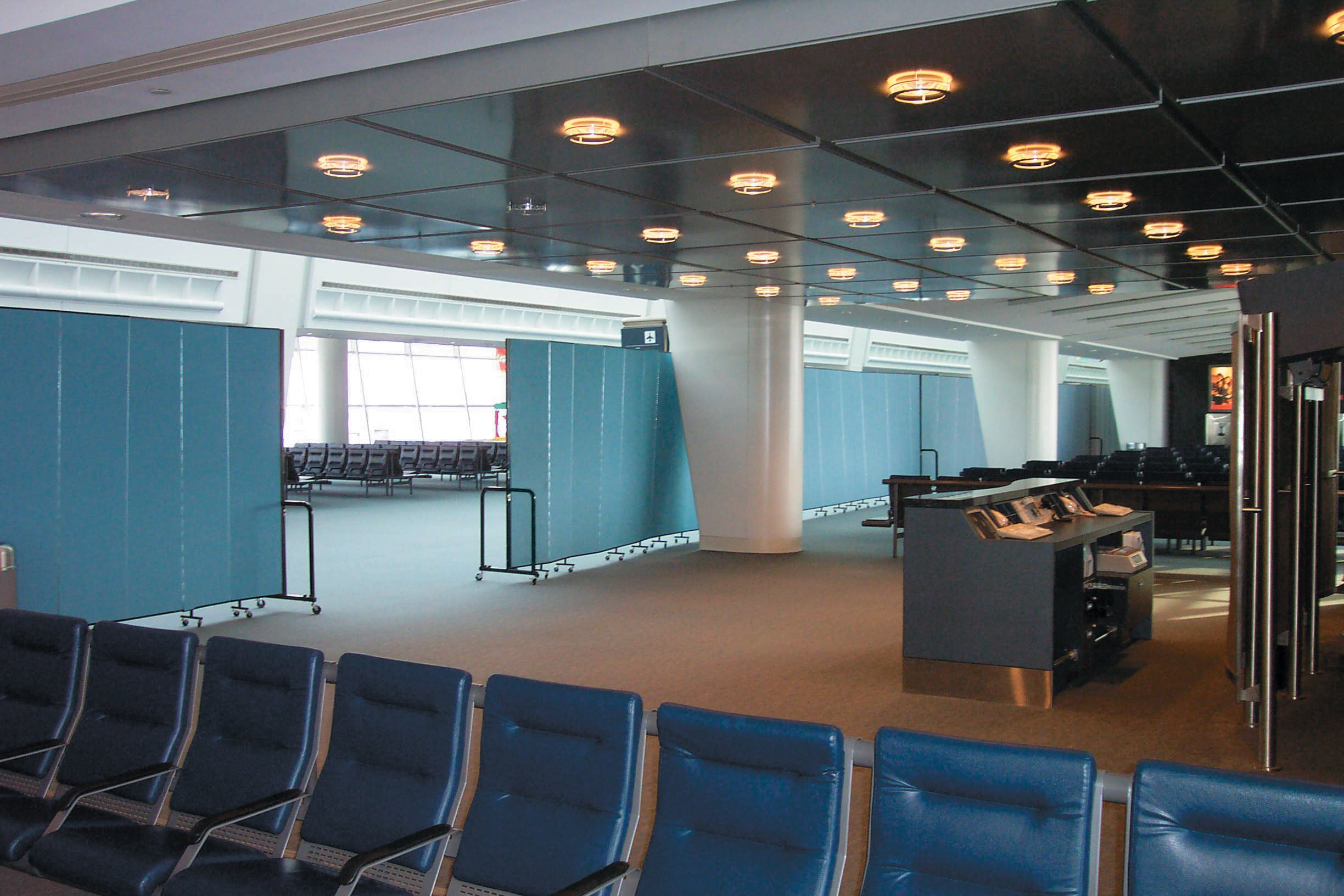 A continuous wall of Screenflex Room Dividers separates a vacant airport terminal from a walkway.