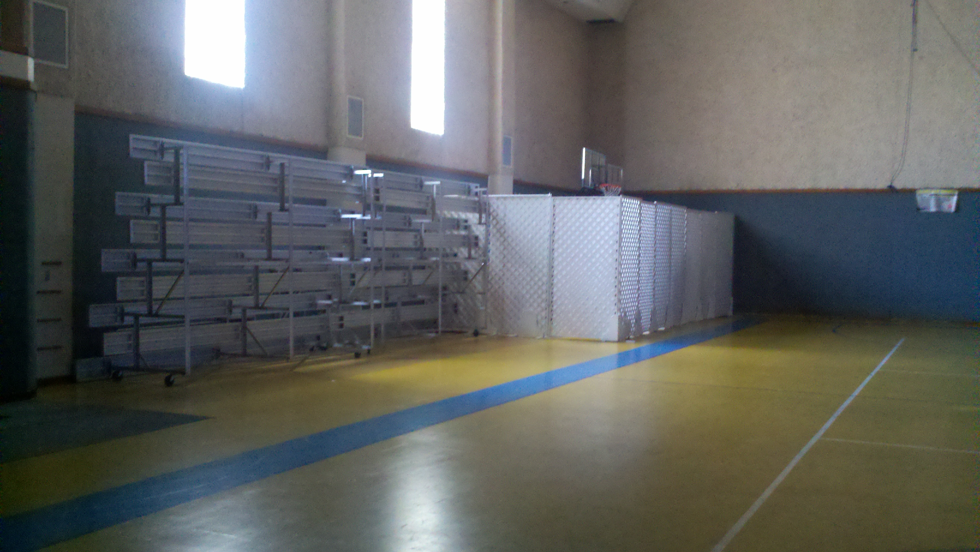 Metal bleachers folded against a wall next to fabric covered lattice shielding basketball equipment