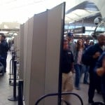 A row of Screenflex Room Dividers separate passengers walking from waiting areas in an airport.