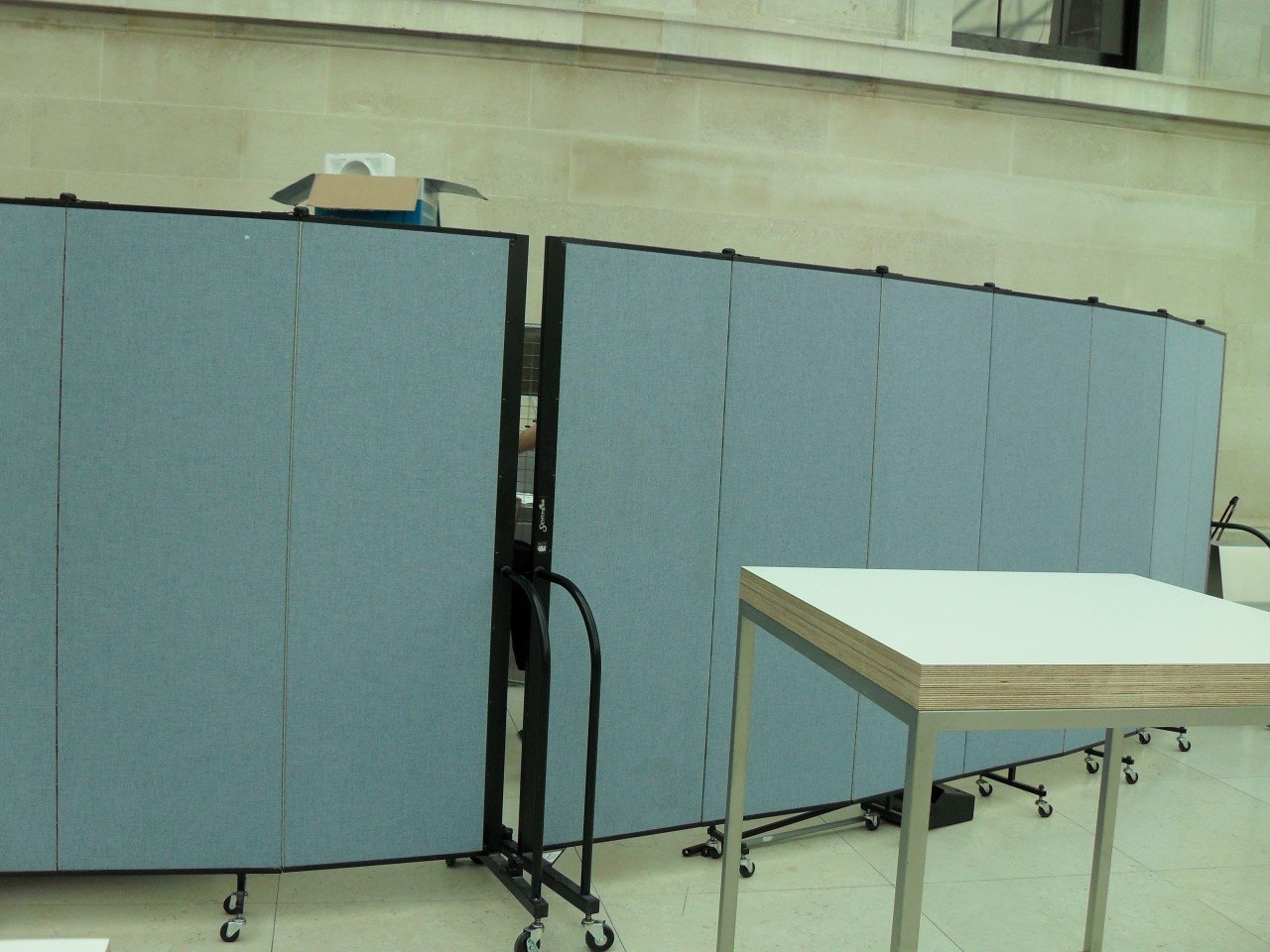 Screenflex Room Divider restrict access to a storage area in a room.