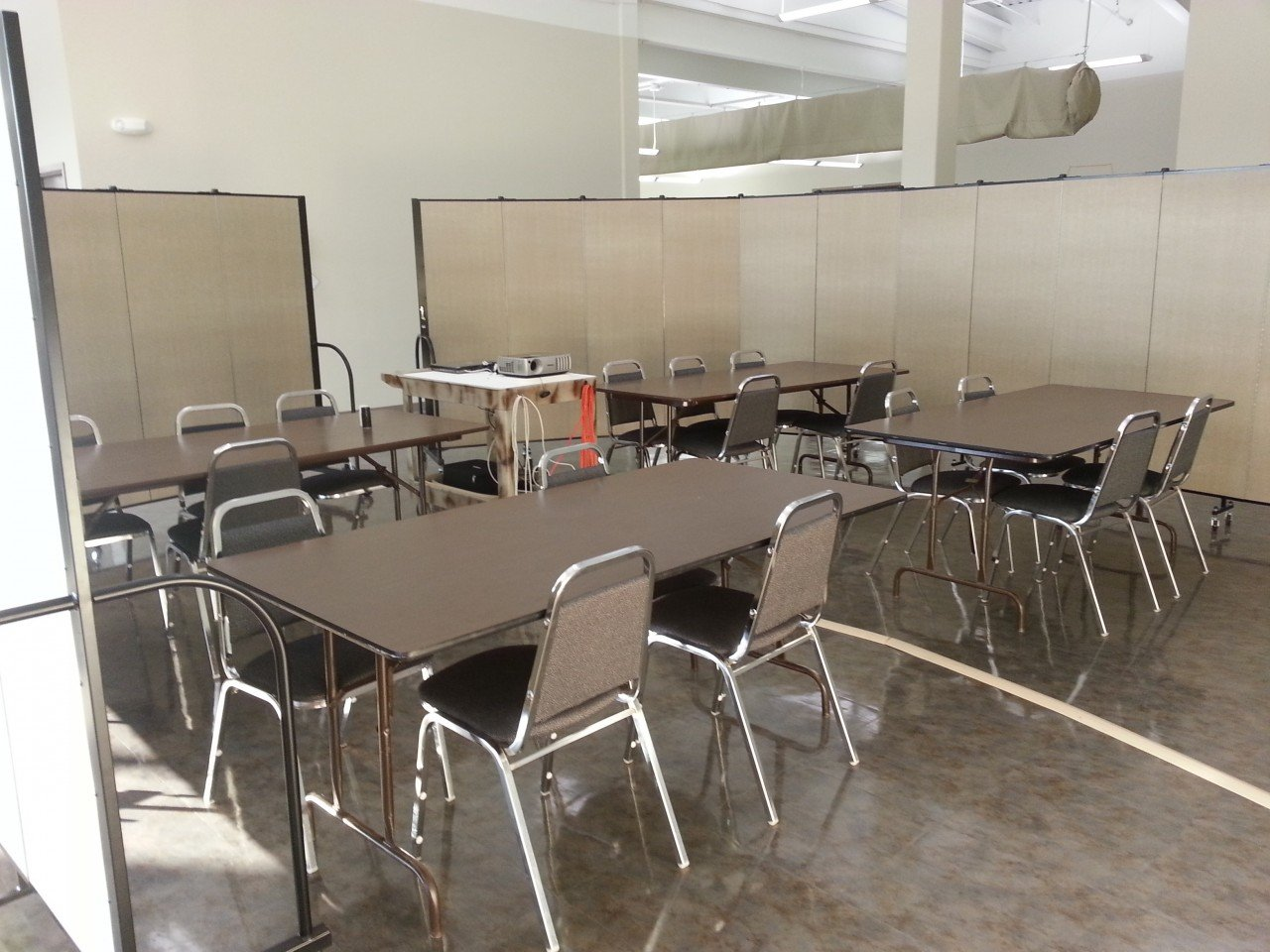 4 rectangular tables and chairs surround a projector in a temporary meeting room created with Screenflex Room Divider walls.