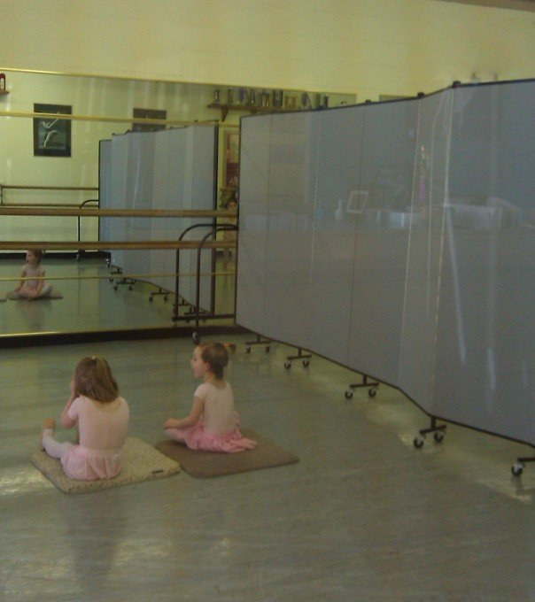 Two young dancers in pink leotards sitting on a mat in a dance studio