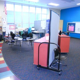 Screenflex Room Divider arranged as a curved wall to divide a classroom into two learning areas.