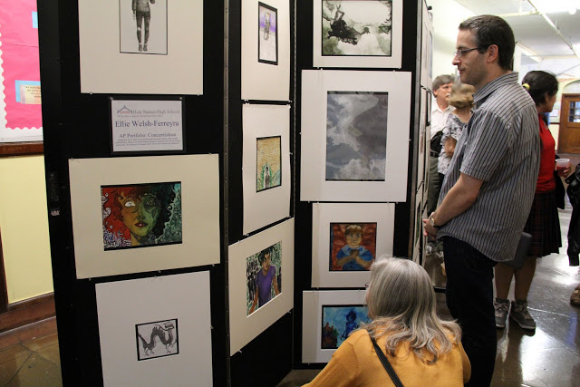 Gallery goers look at art displayed on display panels in a hallway.