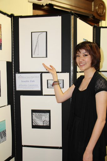 Female art student points to her charcoal drawing displayed on a Screenflex Room Divider at an art gallery.