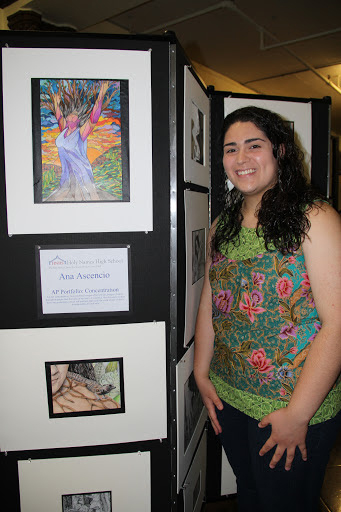 Female stands next to her drawing displayed on Screenflex Room Divider at a student art gallery.