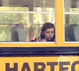 Elementary aged girl looks through a bus window as she sits by herself.