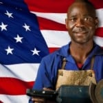 A male in an industrial apron stands in front of the American flag
