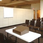 A room divider separates a room into a lecture hall and dining room