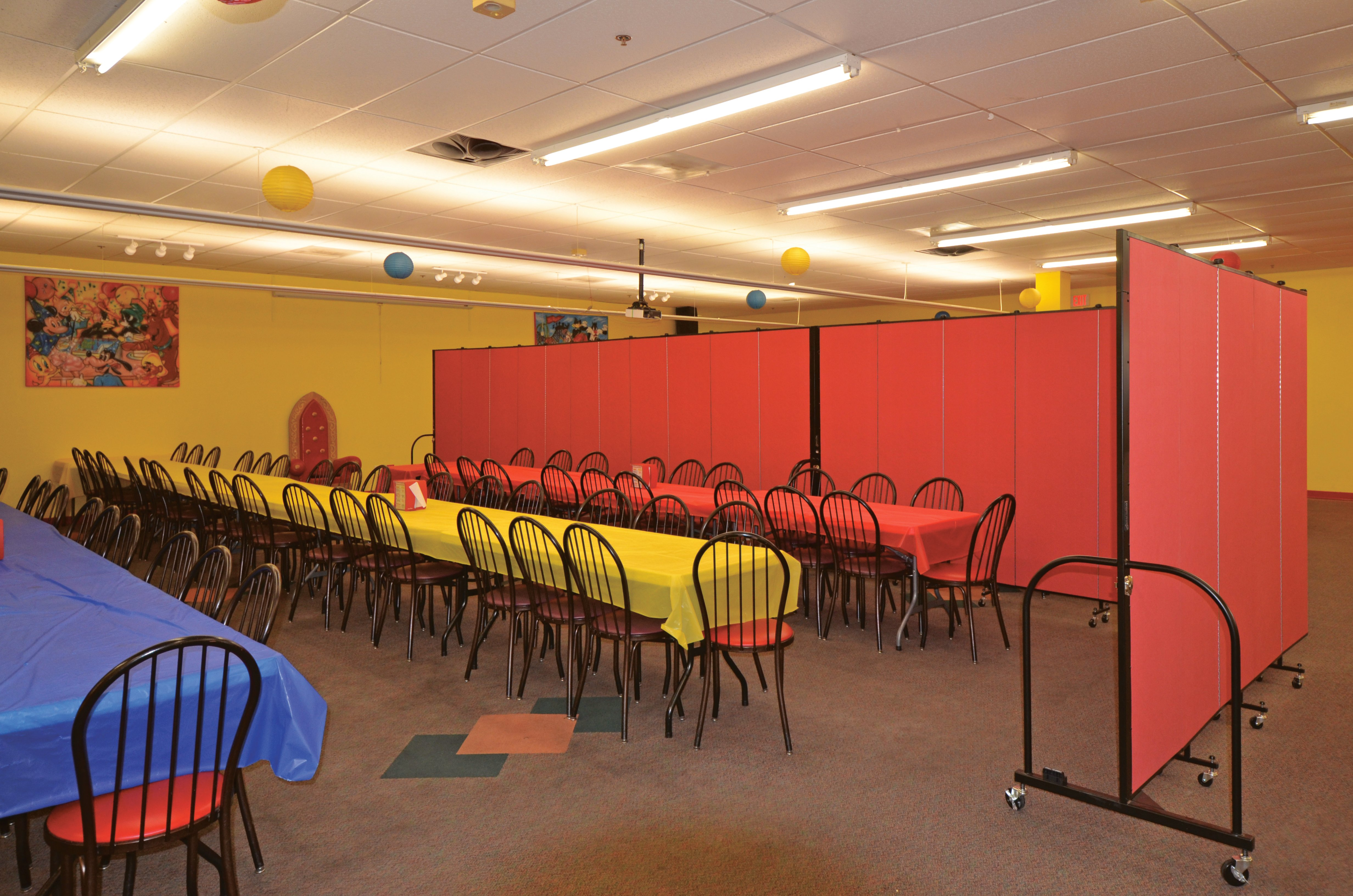 A colorful party room is divided into two eating areas with a red Screenflex Room Divider.