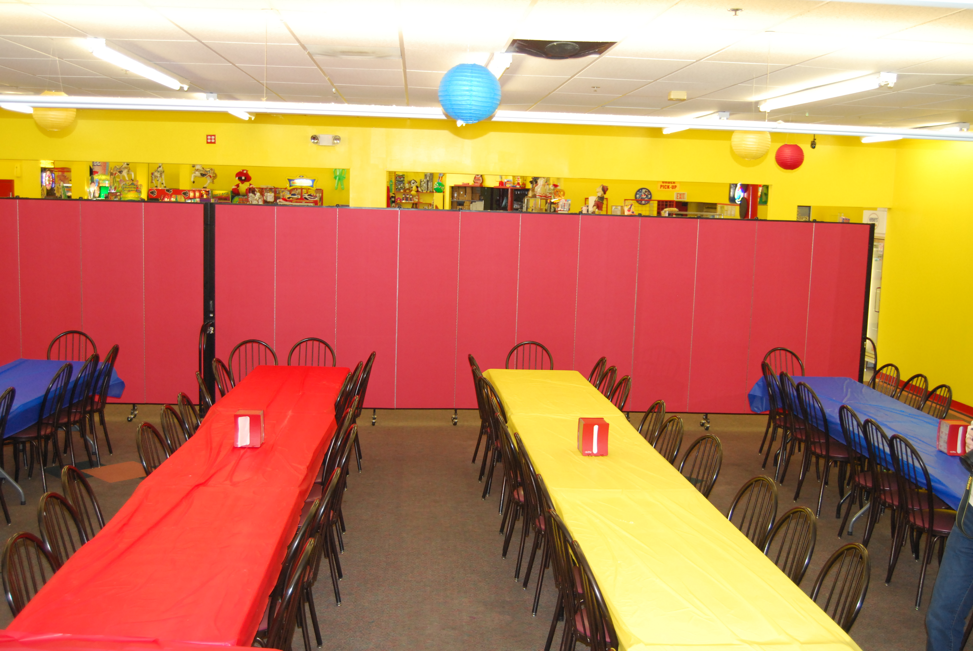 2 connected room dividers create a wall separating a party room from games at an indoor amusement center.