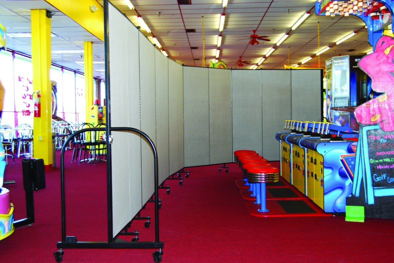 Screenflex Room Divider separates cafeteria from game room at an indoor game center.