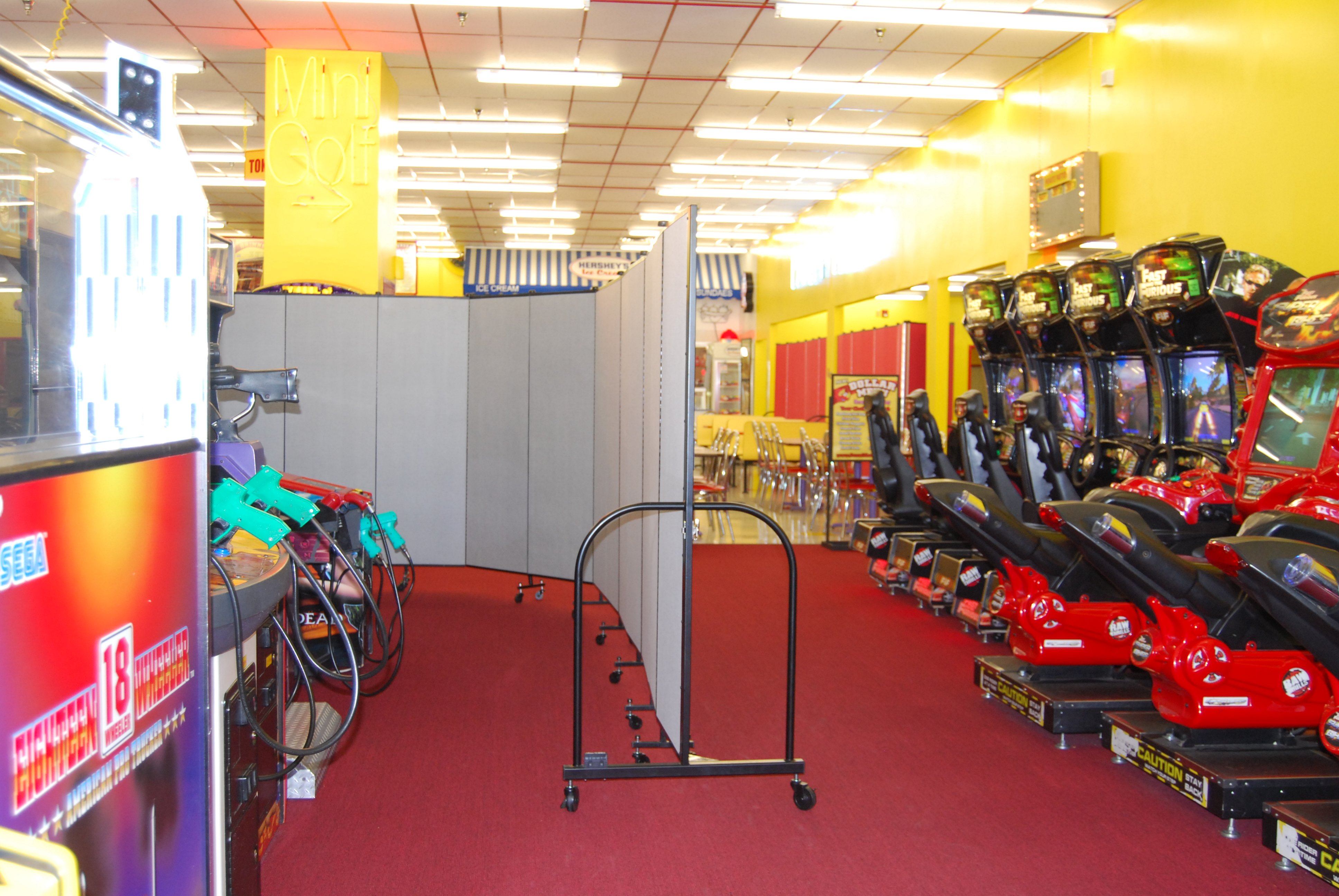 portable crowd control barrier at an indoor amusement park to separate games from dining area.