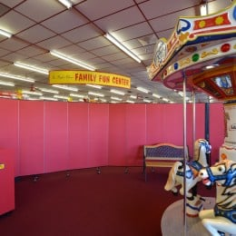 Two red Screenflex Room Dividers connected to create a curved barrier wall between a merry go round and a cafeteria at a family fun center.