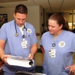 A male and female medical staff review patient records.